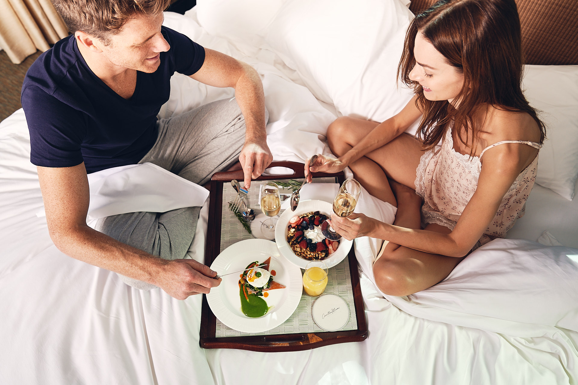 Couple having breakfast in bed at the Carillon Miami lifestyle photo shoot