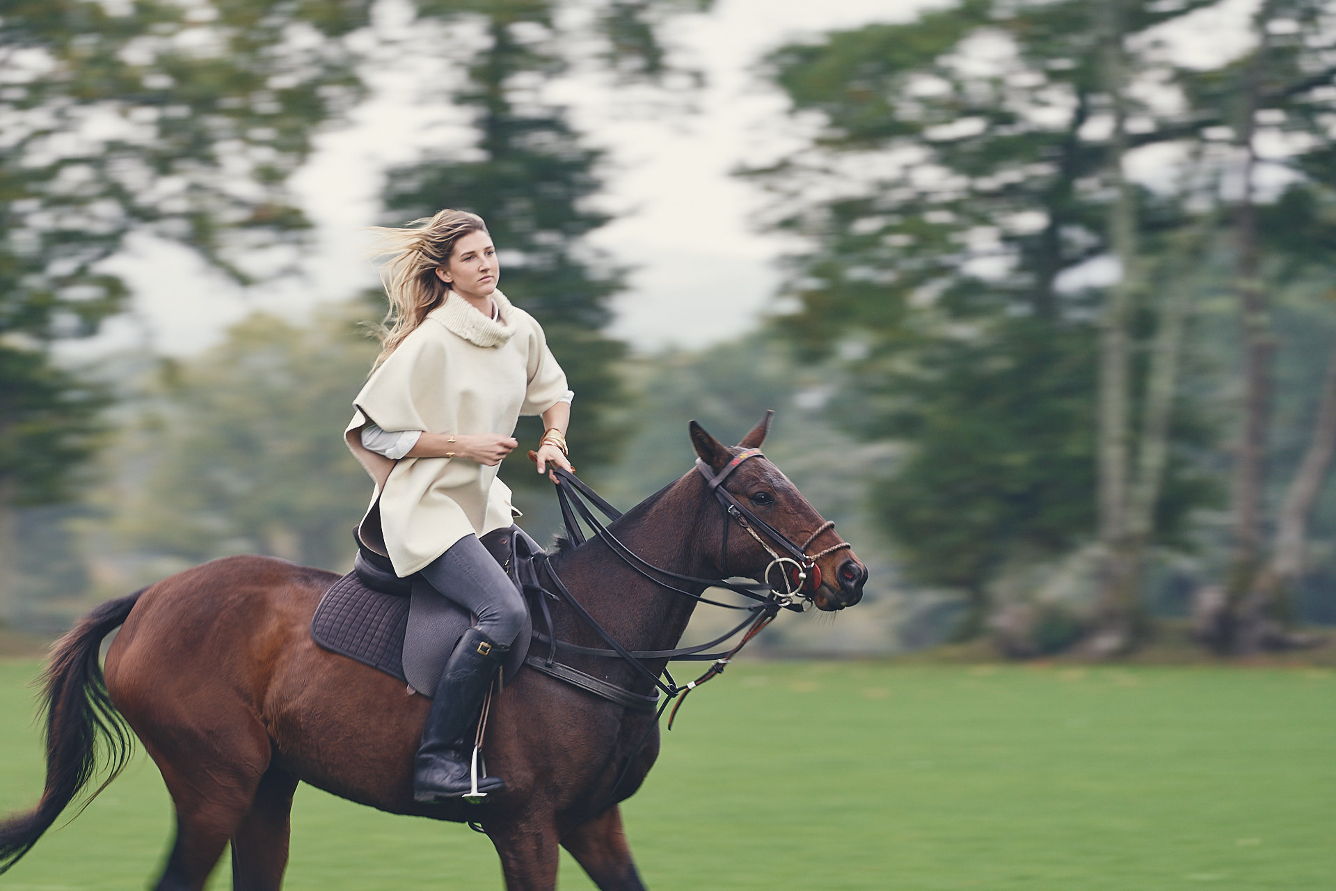 Riding a polo pony wearing a poncho by Stick & Ball English Photo Shoot
